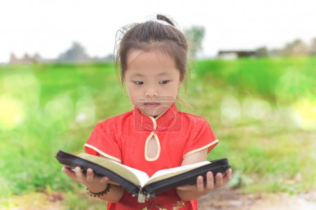 Photo for Little Girl reading bible in spring park . Portrait cute child in chinese dress. - Royalty Free Image