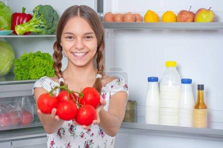 Photo pour Souriant la belle jeune fille de l'adolescence retenant les tomates rouges fraîches tout en restant près du réfrigérateur ouvert dans la cuisine à la maison. Verticale de joli enfant choisissant la nourriture dans le réfrigérateur complètement des produits sains. - image libre de droit