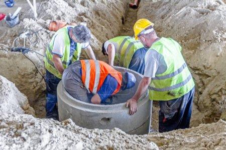 Photo pour Les travaux sont en cours. Les travailleurs de la construction assemblent un nouveau trou d'homme en béton sur le chantier . - image libre de droit
