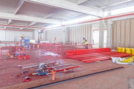 Photo pour Les travailleurs sont peinture longtemps autour des tuyaux en rouge à l'aide d'un aérographe sur chantier. - image libre de droit