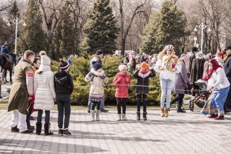 Maslenitsa- Girls jumping through a jumper in the park at Carni