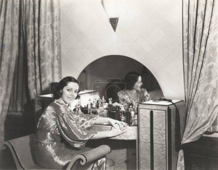 woman sitting at dresser