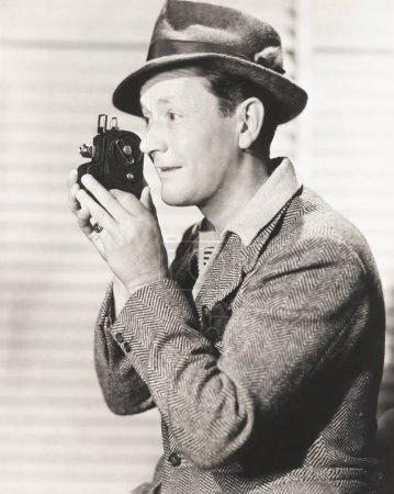 man photographing through camera