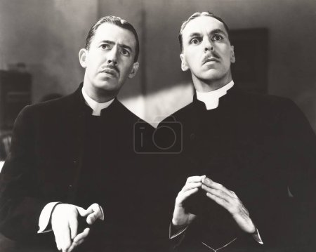 Priests clasped looking away