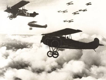 Biplanes flying in cloudy sky