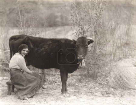woman sitting by cow