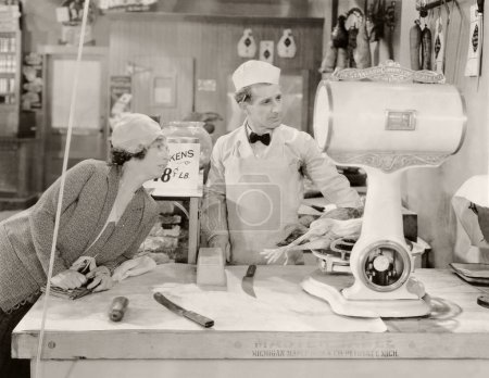 Butcher and customer looking at weight