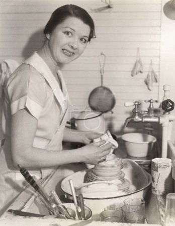 maid wiping cup in kitchen
