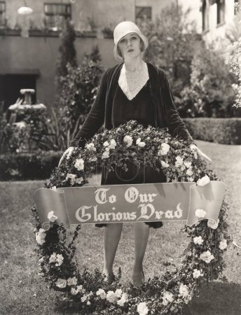 woman holding wreath with sign