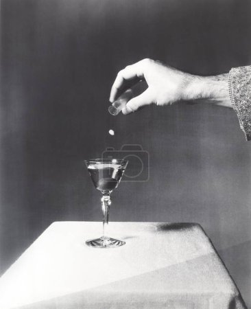 hand adding medicine in drink