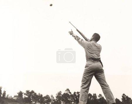 Photo pour Skeet homme tir contre le ciel clair - image libre de droit