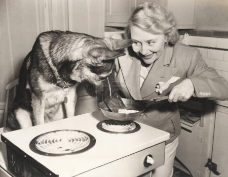 woman showing food to German Shepherd