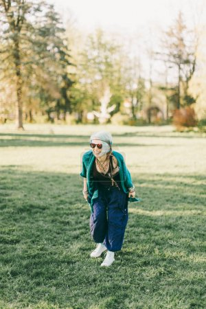 Young hippie woman with blue hair having fun in green park, full length
