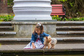 child girl playing with a Yorkshire Terrier