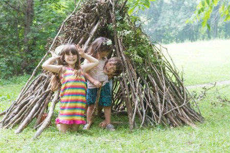 kids playing next to wooden stick house