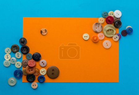 buttons and orange sheet of paper on a blue background