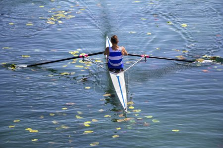 A Young single scull rowing competitor paddles on the tranquil l