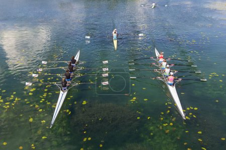 Young athletes rowing on the tranquil lake