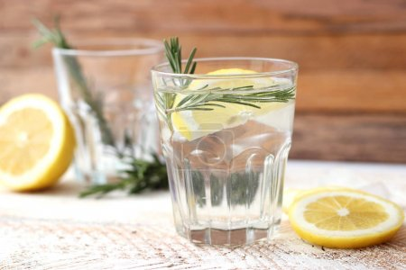 Photo for Water in a glass with lemon and rosemary on a wooden background. Cooling and fresh drinks. - Royalty Free Image