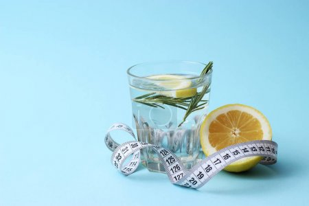 Photo for Water with rosemary and lemon and centimeter tape with a place for inserting the text. concept of health, diet, fitness, healthy digestion, metabolism. minimalism, the top - Royalty Free Image