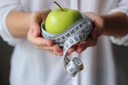 Photo for Centimeter tape and a green apple in female hands on a light background. minimalism, diet, fitness, healthy nutrition, vitamins. Concept of health, body. - Royalty Free Image