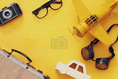 Photo pour Vue de dessus de l'avion jouet jaune vintage, vieil appareil photo, lunettes de pilote et valise - image libre de droit