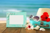 Fedora hat, sunglasses, tropical hibiscus flower next to blank frame over wooden table and beach landscape background