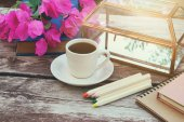 Books, colorful pencils and cup of coffee on old wooden table outdoor in the park