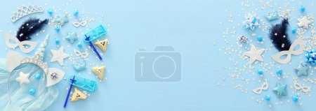 Purim celebration concept (jewish carnival holiday) over pastel blue wooden background. Top view, Flat lay