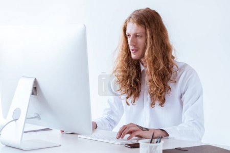 stylish tattooed businessman with ginger long hair working with computer in workspace