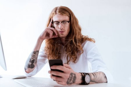 stylish tattooed businessman with curly hair using smartphone at table in office