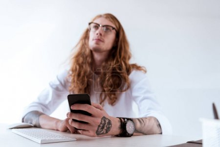 pensive stylish tattooed businessman with curly hair holding smartphone and looking up