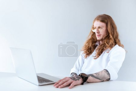 side view of stylish tattooed businessman with curly hair looking at laptop