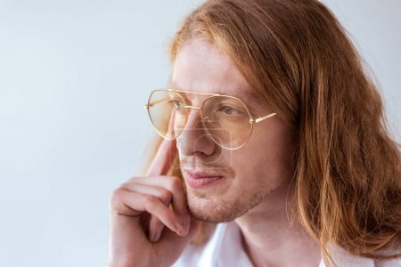 portrait of pensive stylish businessman with curly hair and glasses isolated on white