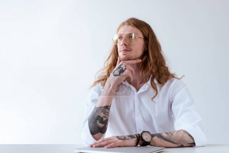 Photo for Pensive stylish tattooed businessman with curly hair looking away isolated on white - Royalty Free Image