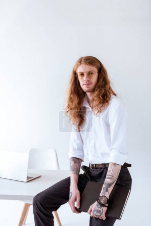 Photo for Stylish tattooed businessman with curly hair sitting on table and looking at camera in office - Royalty Free Image