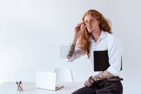 stylish tattooed businessman with curly hair sitting on table and touching glasses in office