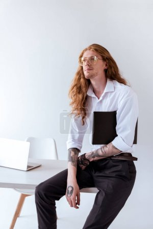 stylish tattooed businessman with curly hair sitting on table and looking away in office
