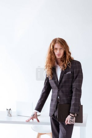stylish tattooed businessman with curly hair standing near table and holding folder