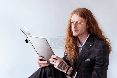 stylish tattooed businessman with curly hair reading documents