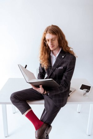 Photo for Stylish tattooed businessman with curly hair sitting on table and reading documents - Royalty Free Image