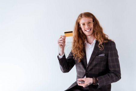 smiling tattooed businessman with curly hair showing credit card isolated on white