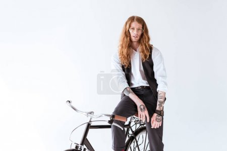 stylish tattooed businessman with long ginger hair sitting on bicycle isolated on white