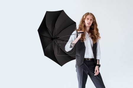 Photo for Fashionable businessman with ginger hair holding black umbrella isolated on white - Royalty Free Image