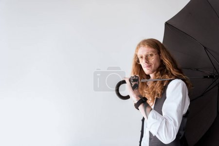 side view of stylish tattooed businessman with ginger hair holding black umbrella isolated on white