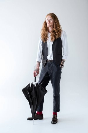 stylish tattooed businessman with curly hair standing with black umbrella and looking away