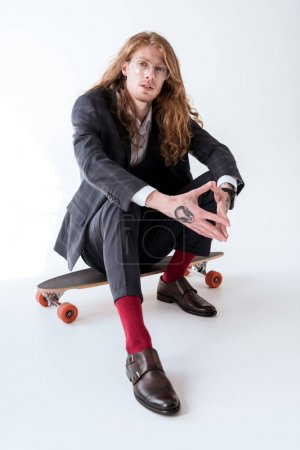 Photo for Stylish businessman with curly hair sitting on skateboard - Royalty Free Image