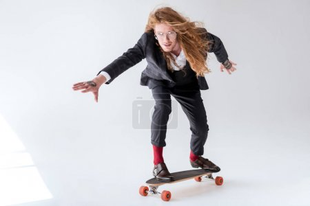 stylish businessman with curly hair skating on longboard