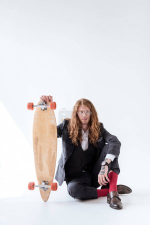 stylish businessman with curly hair sitting on floor and holding skateboard