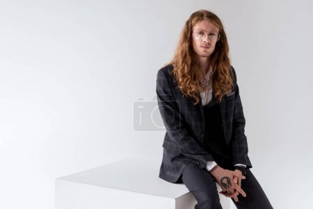 stylish tattooed businessman with curly hair sitting on white cube isolated on white